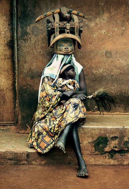 mujer africana con una mascara tallada de madera