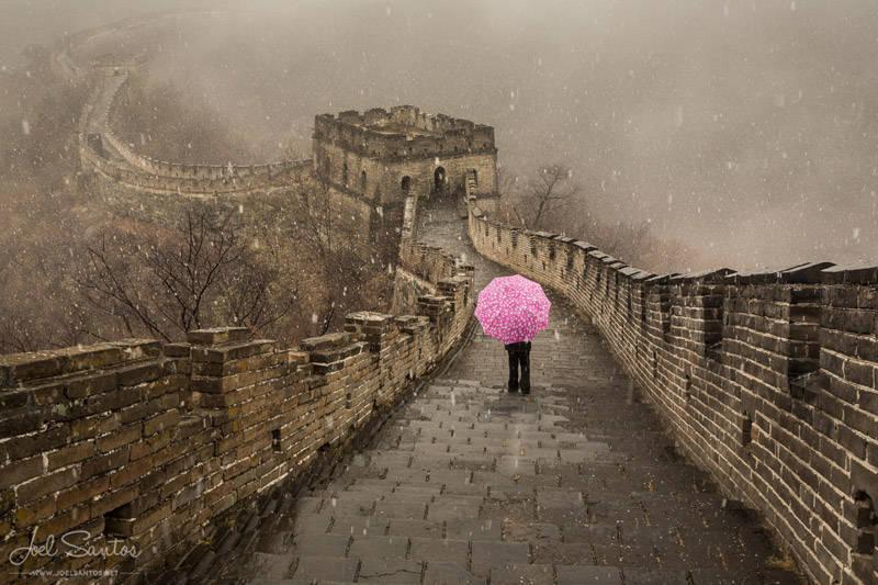 Mujer con sombrilla rosa bajo la nieve, La Gran Muralla China. Fotografía de Joel Santos.