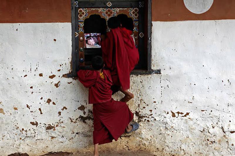 Monjes en Bután viendo la televisión