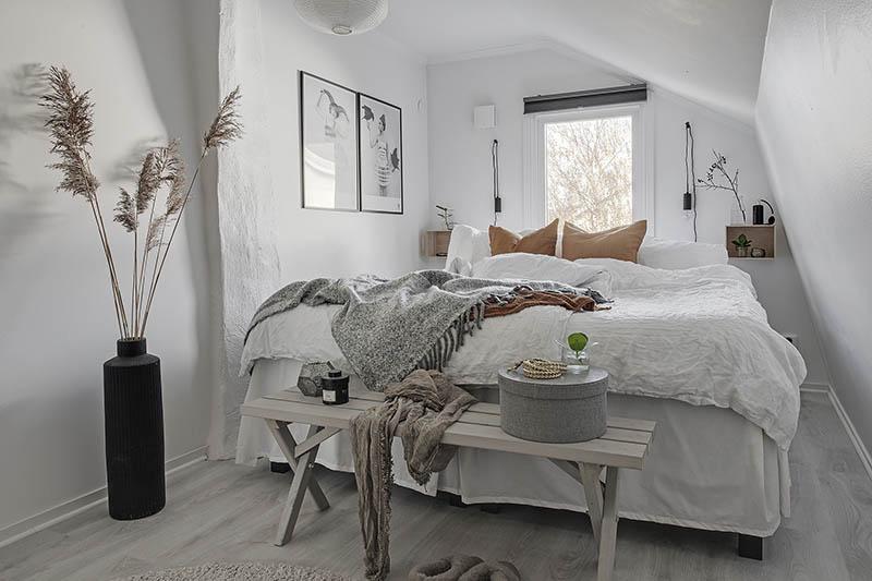 Un banco a los pies de la cama en un dormitorio pequeño