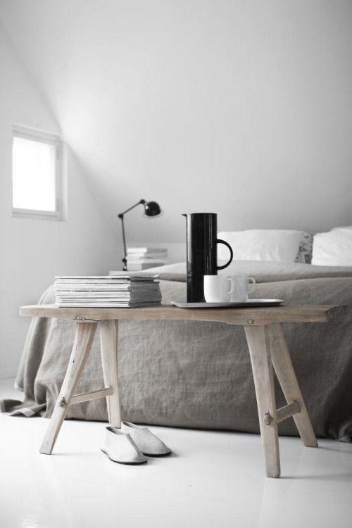 banco de madera como mesa auxiliar en un dormitorio