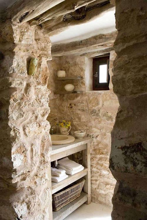 Baño rústico con paredes de piedra