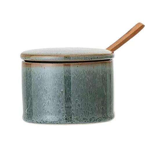 tarro verde de cerámica con tapa y cuchara de madera