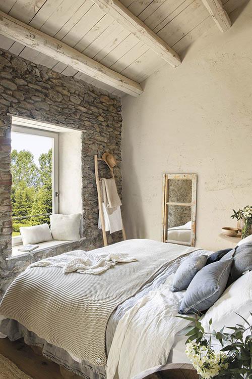 dormitorio rústico con pared de piedra
