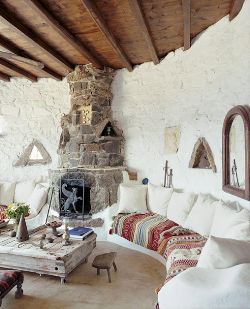 paredes blancas, piedra y una chimenea en una casa griega