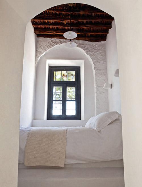 Vigas de madera y paredes blancas en un dormitorio de una casa rural