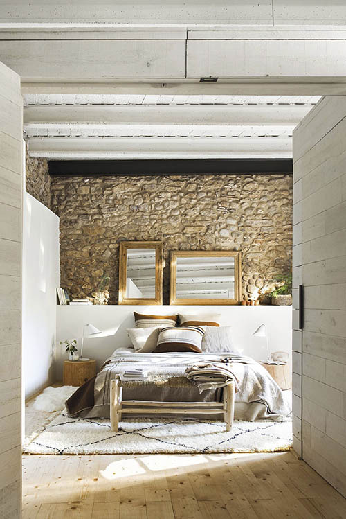dormitorio con pared de piedra
