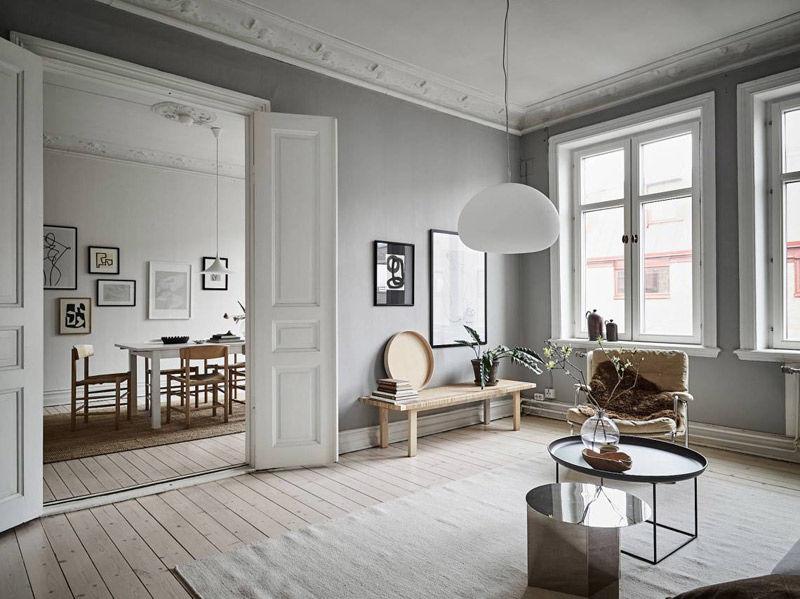 Tonos de madera y muebles contrastando con el gris de la pared en un salon de estilo nórdico