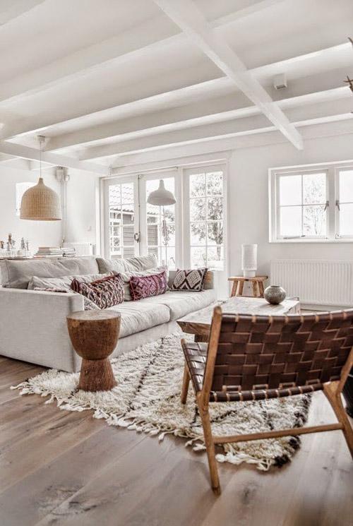 Salón blanco con suelo de madera y detalles decorativos étnicos