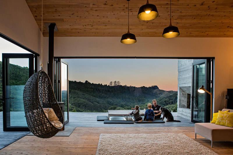 Silla colgante de mimbre de color negro en una casa de madera