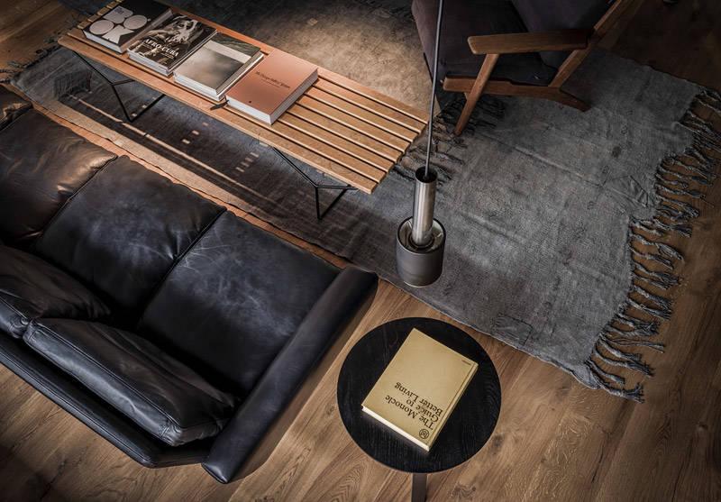 Sillón de cuero desgastado y lámpara vintage de inspiración industrial