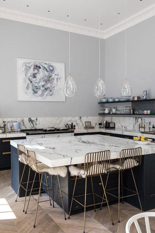 isla de cocina de mármol con sillas metálicas